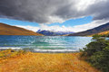 The gale on the emerald lake thundercloud closes sky in distance mountains with snow capped Stock Image