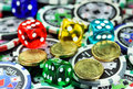 Gamble responsibly five multicolored translucent dice with white numbers set amongst some gambling chips and gold coins asking the Stock Photography