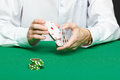 Gambler male hand with cards and chips on green table Stock Photography