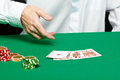 Gambler male hand with cards and chips on green table Royalty Free Stock Images