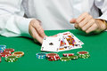 Gambler male hand with cards and chips on green table Stock Photos