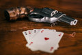 Gambling risky concept gun and four aces cards on wooden table Royalty Free Stock Images