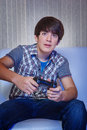 Gamer guy sits in darkness with a game gadget in hands Royalty Free Stock Photos
