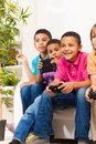 Gamers boys close portrait of a group of diversity looking children and girls friends playing videogame sitting on the sofa in Royalty Free Stock Image