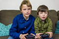 Gaming brothers two little on a couch playing a computer game Royalty Free Stock Images