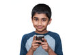 Gaming an handsome indian kid playing games with the mobile phone Stock Photography