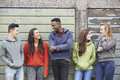 Gang of teenagers hanging out in urban environment smiling Stock Photography