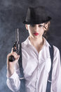 Gangster woman beautiful and dangerous young female holding the gun isolated on dark background Stock Photos