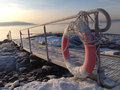 Gangway over the frozen ground and a lifebuoy metal snow leading to water of fiord in oslo norway Stock Photos