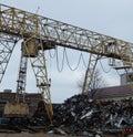 Gantry crane at junkyard unloads vehicle wreckage Royalty Free Stock Photo