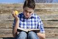 Garçon de portrait young lisant un livre dans des escaliers en bois été Photo libre de droits