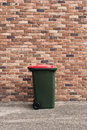 Garbage bin large wheelie trash in front of a brick wall Royalty Free Stock Image