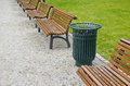 Garbage bin and wooden bench in city park green Stock Image