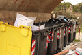 Garbage bins overflowing angled view old plastic dumpsters with Royalty Free Stock Images