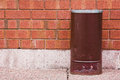 Garbage can grungy on sidewalk with brick wall Stock Photography