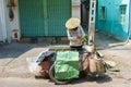 A garbage collector collecting carton boxes on a small street, Saigon, Vietnam