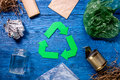 Garbage for recycling with recycling symbol on blue wooden background top view Royalty Free Stock Photo