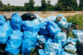 Garbage on river banks bags piled up Stock Photos
