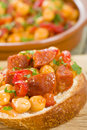 Garbanzos y chorizo tapas chickpeas and spicy sausage with red peppers on crusty bread traditional spanish food Stock Image