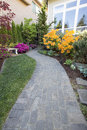 Garden brick paver path walkway with green grass lawn and landscaping plants Royalty Free Stock Photography