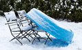 Garden chairs and plastic pool in snowfall Royalty Free Stock Images