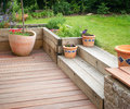 Garden detail with terrace with wooden steps and flowers in flower pots Royalty Free Stock Photo
