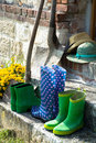 Garden equipment - rubber boots, schovels and srtaw hats in sunn Royalty Free Stock Photo