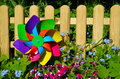 Garden fence pinwheel and flowers and Royalty Free Stock Photos