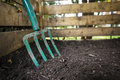Garden fork turning compost black composted soil in wooden bin Stock Photography