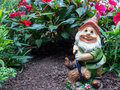 Garden gnome happy in front of secret hole under plants Stock Photo