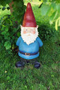 Garden gnome looking at camera big underneath a tree Royalty Free Stock Photos