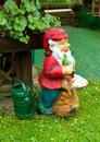 Garden gnome in a next to a watering can Stock Image
