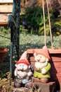 Garden gnomes two in a city set next to a green wrought iron and wooden bench and in front of a teracotta coloured Royalty Free Stock Photos
