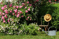 Garden idyll with iron chair and sun hat in the watering can Stock Photos