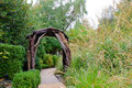 Garden path and arbor a stone passes under a natural wood surrounded by lush green plants Stock Photography