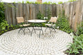 Garden patio with two chairs and round table in front of flowerbed and wooden planks Royalty Free Stock Photo