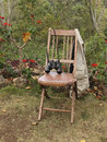 Garden seat a waistcoat and binoculars on a rustic wooden chair in a tropical Stock Images