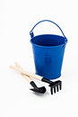 Garden shovel, rake and blue metal bucket isolated Royalty Free Stock Photo