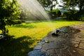Garden sprinkler splash of water from irrigation running water in the Stock Photos