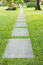 Garden stone path with grass growing up between the stones Stock Photography