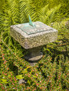 Garden sundial a small stone surrounded by plants in a formal Stock Image