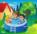 Garden with three kids in pool Royalty Free Stock Images