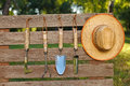 Garden tools on board fence and straw hat in Stock Photos