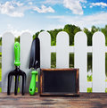 Garden tools and equipment and a white fence on a landscape Royalty Free Stock Photos