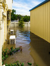 Garden under flood water view down the side of a house during brisbane floods air conditioning units and garage are in Stock Images