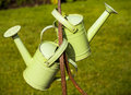 Garden watering cans two green hanging from an iron pole Royalty Free Stock Photography