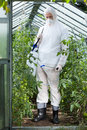 Garden worker in protective clothing spraying plants Stock Photography