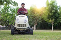 Gardener cutting the grass of a garde on a lawn mower Royalty Free Stock Photo