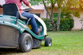 Gardener cutting the grass of a gardenon a lawn mower Royalty Free Stock Photo