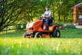 Gardener driving a riding lawn mower in garden Royalty Free Stock Photo